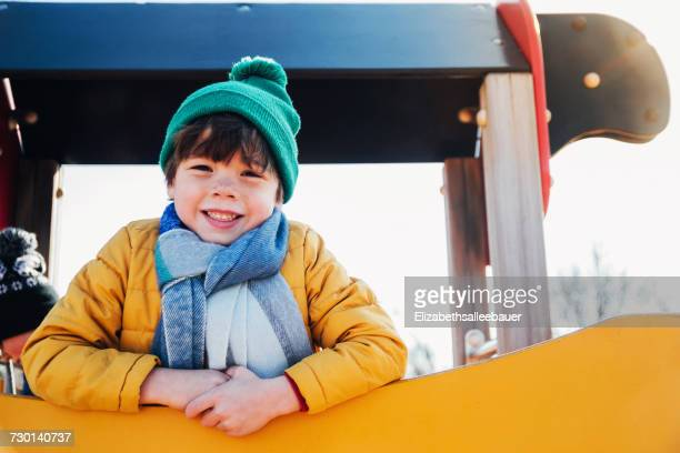 Boy in warm clothing standing on climbing frame in playground