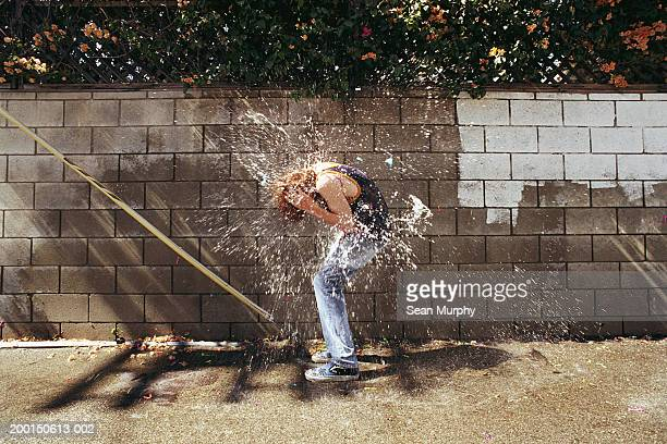boy (13-15) in water fight, being hit with water balloons - wet jeans stock photos and pictures