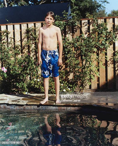Boy (11-13) in wet swimming trunks, standing at edge of pool, portrait