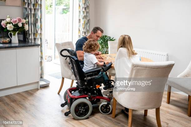 boy in wheelchair doing jigsaw with parents - wheelchair stock pictures, royalty-free photos & images