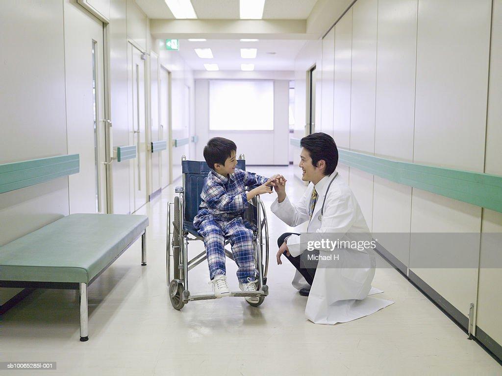 Boy (5-6) in wheelchair, talking to doctor in hospital corridor : Foto stock