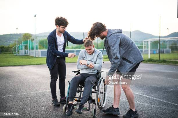 A boy in wheelchair with hurt arm and teenager friends doing sport outside.