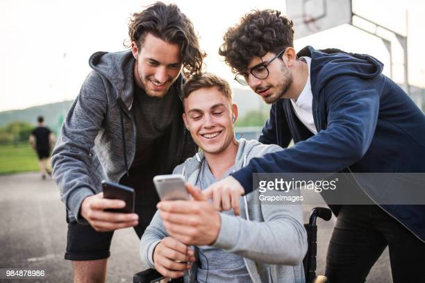 A boy in wheelchair with smartphone and teenager friends taking selfie.