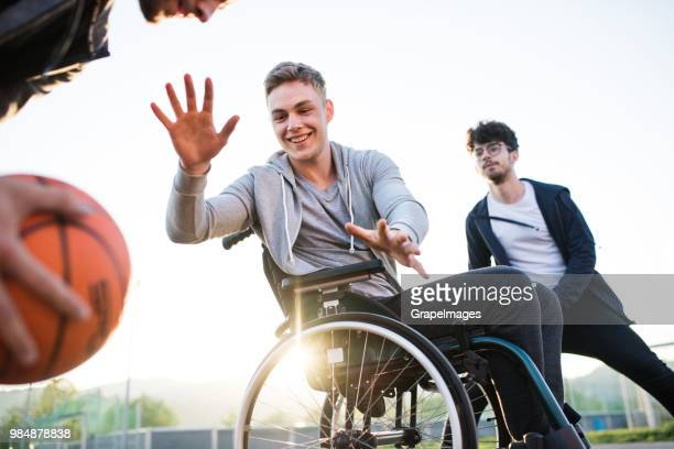 a boy in wheelchair with teenager friends outside playing basketball. - basketball sport stock pictures, royalty-free photos & images