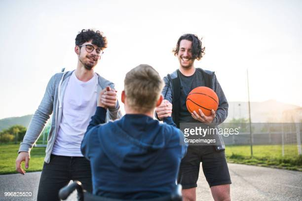 A boy in wheelchair with teenager friends shaking hands outside after playing basketball.