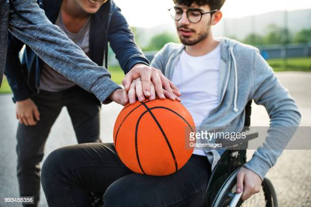 A boy in wheelchair with unrecognizable friends holding a basketball ball.