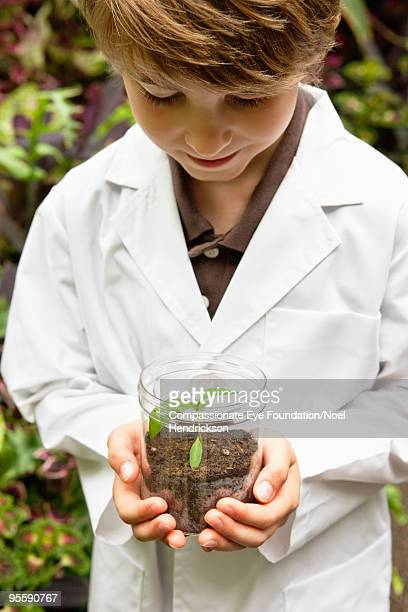 "boy in white lab coat holding a small plant - ""compassionate eye"" fotografías e imágenes de stock"