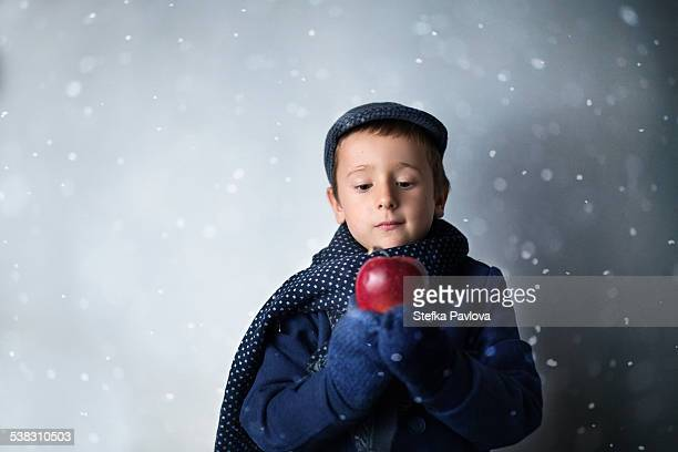 Boy in winter clothes holding red apple in hands