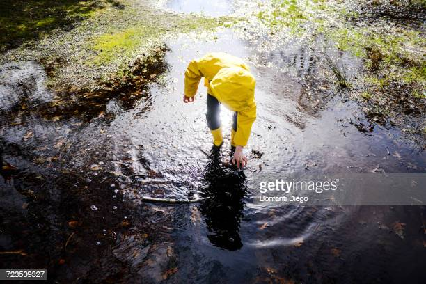 Boy in yellow anorak bending forward in park puddle