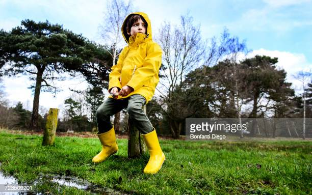 Boy in yellow anorak sitting on park fencepost