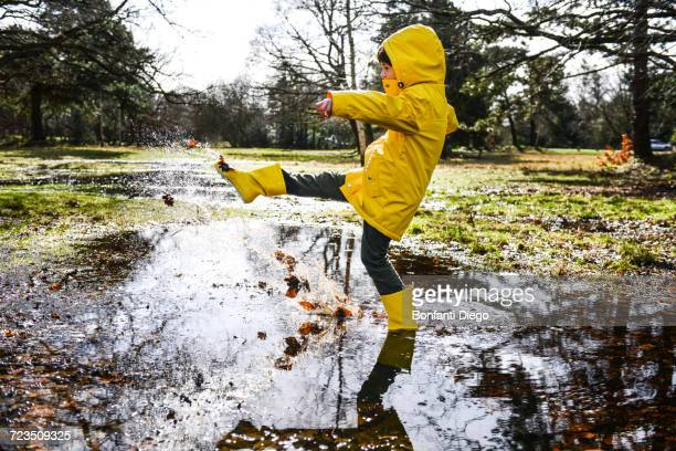 Boy in yellow anorak splashing in park puddle