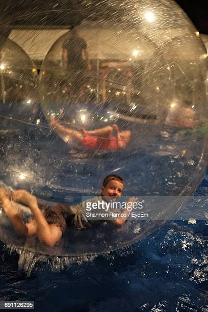 Boy In Zorb Ball Floating On Water At Gage County Fair During Night