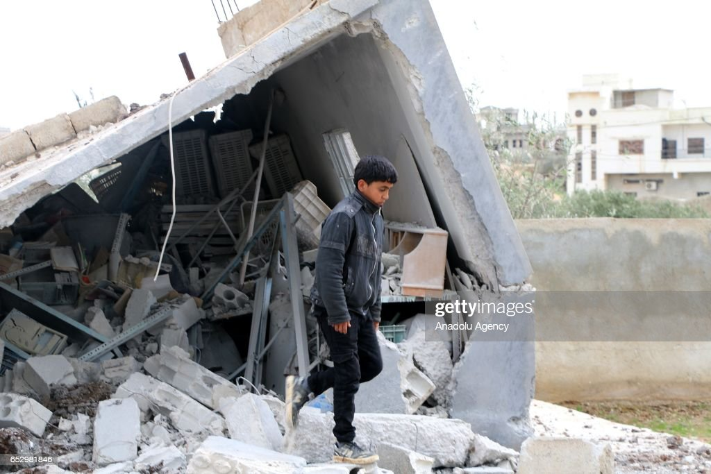 A boy inspects the debris of a building after warcrafts belonging to Assad Regime forces carried out airstrike in Umm al-Mayadeen district of Daraa, Syria on March 13, 2017.