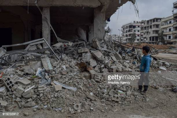A boy inspects the debris of buildings after Assad Regime's airstrikes and ground attacks to Harasta town in the besieged Eastern Ghouta in Damascus...