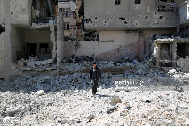A boy inspects the debris of buildings after warcrafts belonging to Assad Regime forces carried out airstrikes to Jisreen town of Eastern Ghouta...