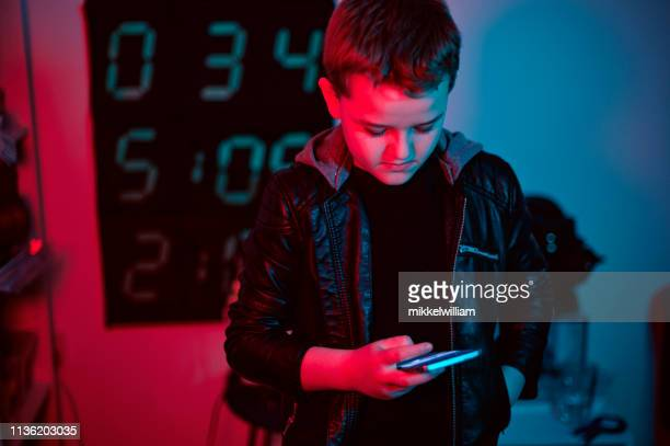 Boy is alone at night and type on his smart phone while looking at the screen