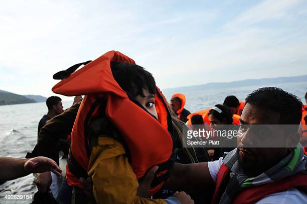 A boy is carried ashore moments after his arrival with other Syrian and Iraqi migrants on the island of Lesbos from Turkey on October 14 2015 in...