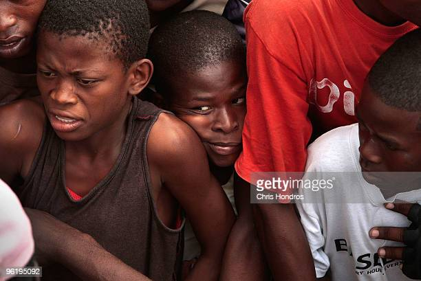 A boy is crowded between other displaced Haitians during water distribution for earthquake victims January 26 2010 in Leogane Haiti The historic town...
