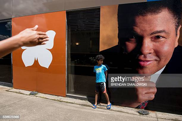 TOPSHOT A boy is directed as he poses with a photo of boxing legend Muhammad Ali June 7 2016 in Louisville Kentucky / AFP / Brendan Smialowski