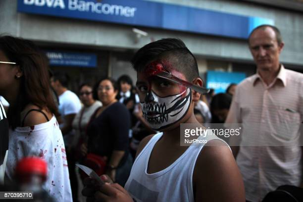 A boy is disguised as a Skull with a fork on his forhead walks during the annual procession of zombies in Mexico City on November 4 2017 Hundreds...