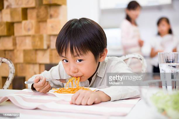 A boy is eating pasta and gazing at camera