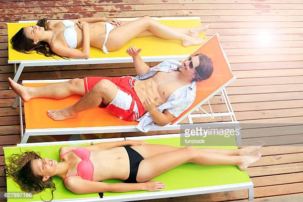 boy is entertaining two girlfriends on sunbed by the pool - girls sunbathing stock photos and pictures