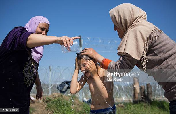A boy is given a wash in front of the border fence at the Idomeni refugee camp on the Greek Macedonia border on March 20 2016 in Idomeni Greece...