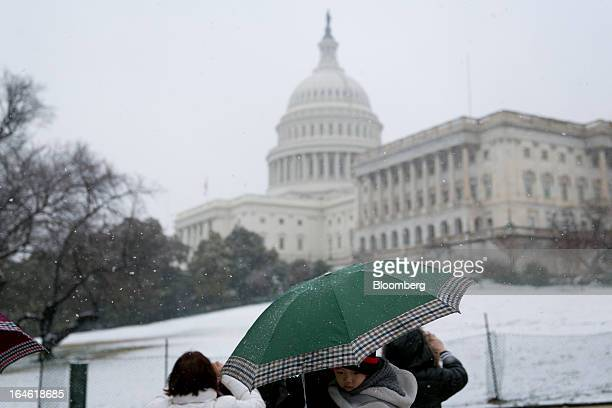 A boy is held underneath an umbrella outside the US Capitol in Washington DC US on Monday March 25 2013 An early spring snowstorm tied up air traffic...