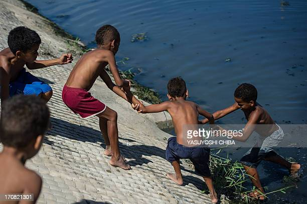 A boy is helped by friends after getting into stinking water to recover a ball which fell there during a football game in a shantytown of Olinda...