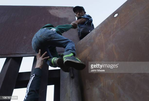 A boy is hoisted by fellow members of the migrant caravan over the USMexico border fence on December 2 2018 from Tijuana Mexico Numerous members of...