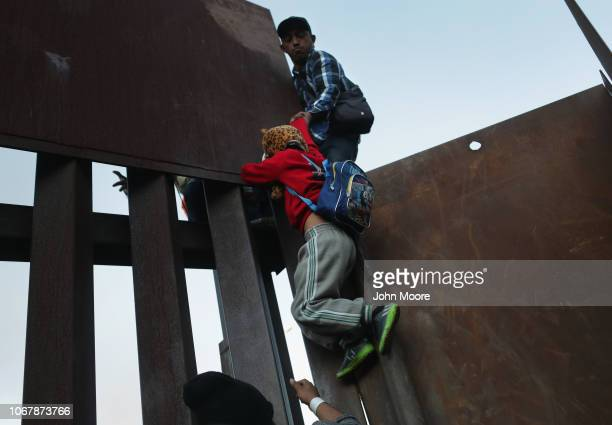 Boy is hoisted by fellow members of the migrant caravan while climbing over the U.S.-Mexico border fence on December 2, 2018 from Tijuana, Mexico....