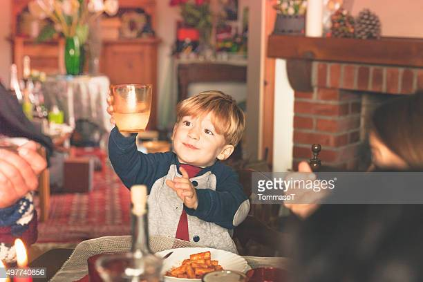 Boy is holding the glass for happy new year's toast