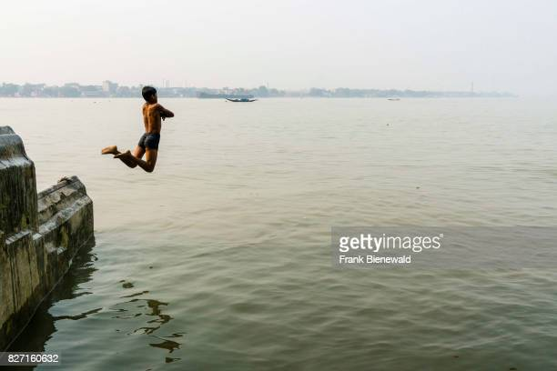 A boy is jumping into the Hoogli River from a wall
