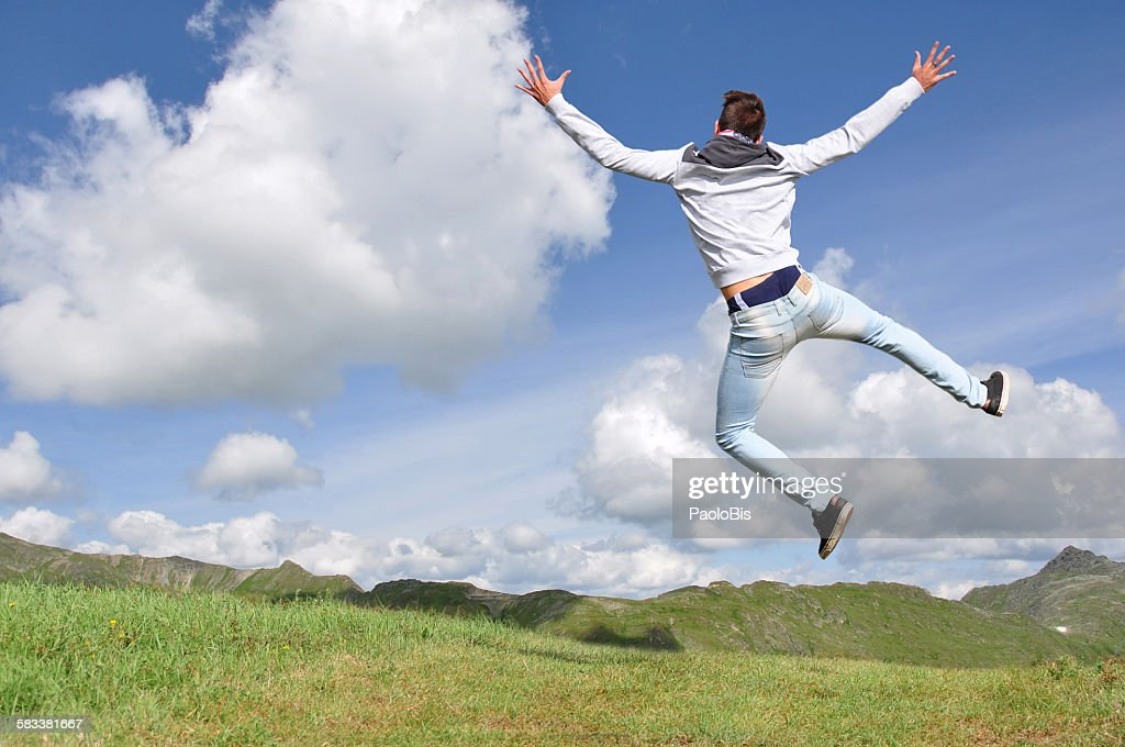 A boy is jumping with mountains in the background : Stock Photo