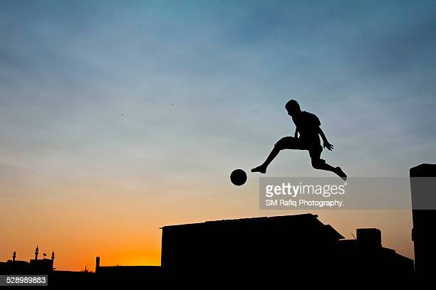 Boy is jumping with soccer ball