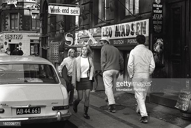 A boy is looking at a girl wearing a mini skirt on a street of Copenhagen Next to them one of the most spread porn shop of Leo Madsen who has...