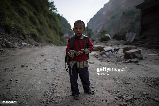 A boy is pictured as he's standing with the destroyed abandoned village behind him on the Araniko Road near the Kobani Village Isolated Nepalese...