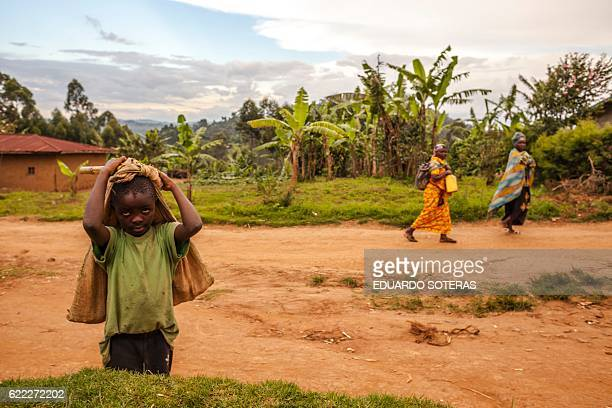 A boy is pictured as women walk past after a working day in the Kyala neighbourhood in Butembo North Kivu province on November 10 2016 Tension...
