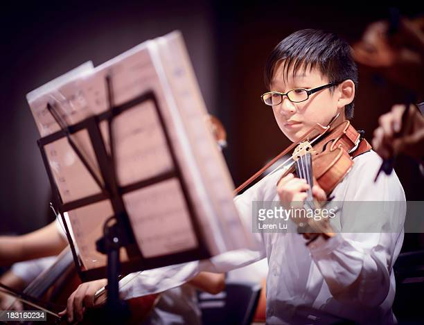 Boy is playing a violin in a concert