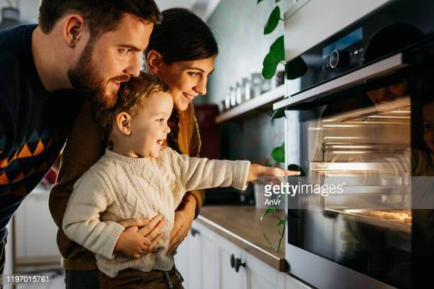 boy is pointing to the owen - oven stock pictures, royalty-free photos & images