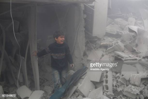 A boy is seen among the debris of buildings as he cries after Assad Regime carried out an airstrike over Arbin town of the Eastern Ghouta region...