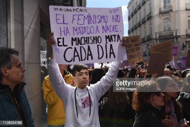 A boy is seen holding a placard reading 'The feminism has not killed anyone the machismo every day' during the protest Thousands of women march in...