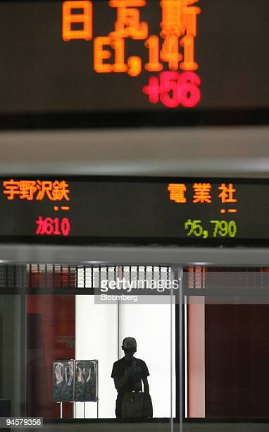 A boy is seen in silhouette behind an electronic stocks indicator at the Tokyo Stock Exchange in Tokyo Japan on Wednesday Sept 19 2007 Asian stocks...