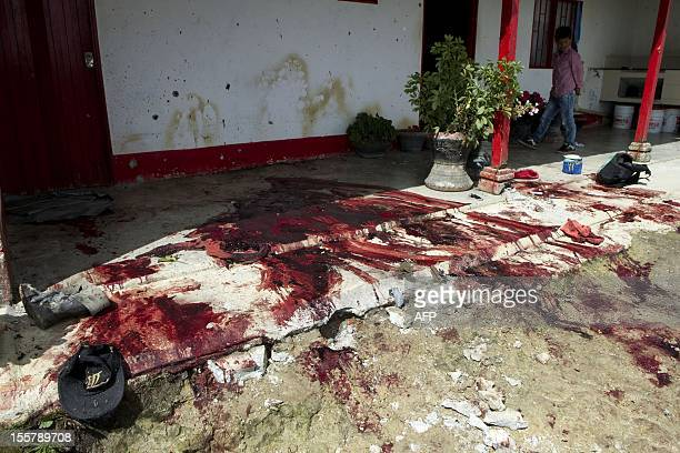 A boy is seen next to a pool of blood at the crime scene where ten people were shot dead by criminal gangs in San Isidro village near Santa Rosas de...