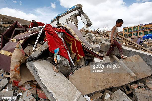 Boy is seen on the debris of collapsed buildings in the earthquake-hit Gyegu town of Yushu County, Qinghai province April 19, 2010. VCP