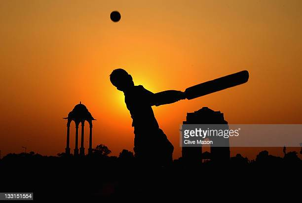 Boy is seen playing cricket against a setting sun at India Gate on October 26, 2011 in Delhi, India.