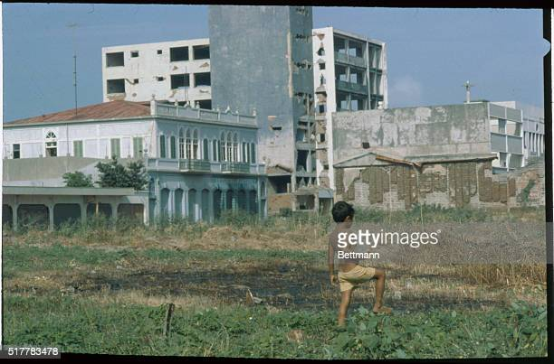 A boy is seen walking near buildings which were damaged by an earthquake in 1972