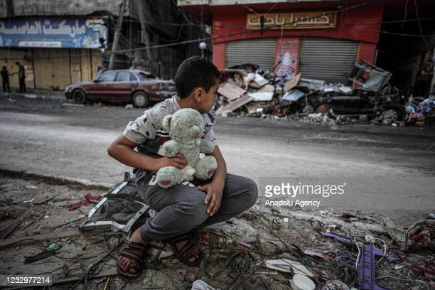 Boy is seen with his teddy bear at damaged site after Israeli army carried out airstrike over a building in Sheikh Ridvan neighbourhood in Gaza City,...