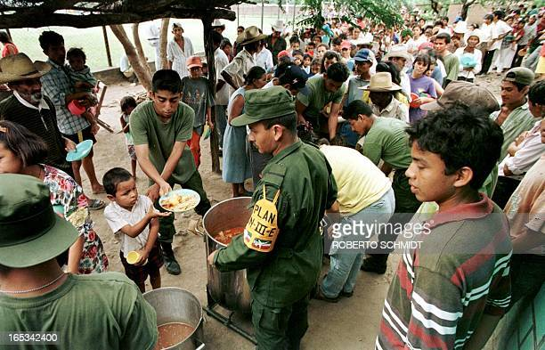 A boy is served a meal by Mexican soldiers in Morolica 09 November eight days after the Choluteca River crested destroying most of the town...