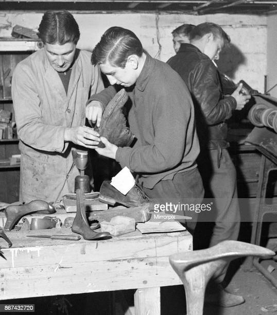 A boy is shown how to replace the heel of a boot He is 'at work' at the Lion Boys Club in Hoxton London where members do shoe repairs for old age...